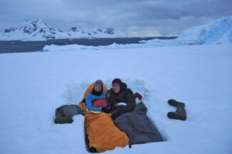 Antarctica camping couple in snow bed