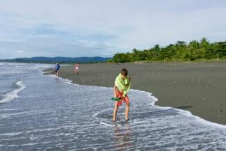 Costa rica osa peninsula casa atrevida boys with grandfather walking on beach