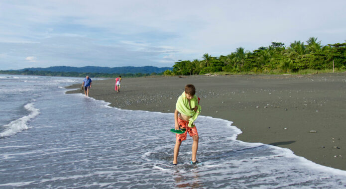 Costa rica osa peninsula casa atrevida boys with grandfather walking on beach