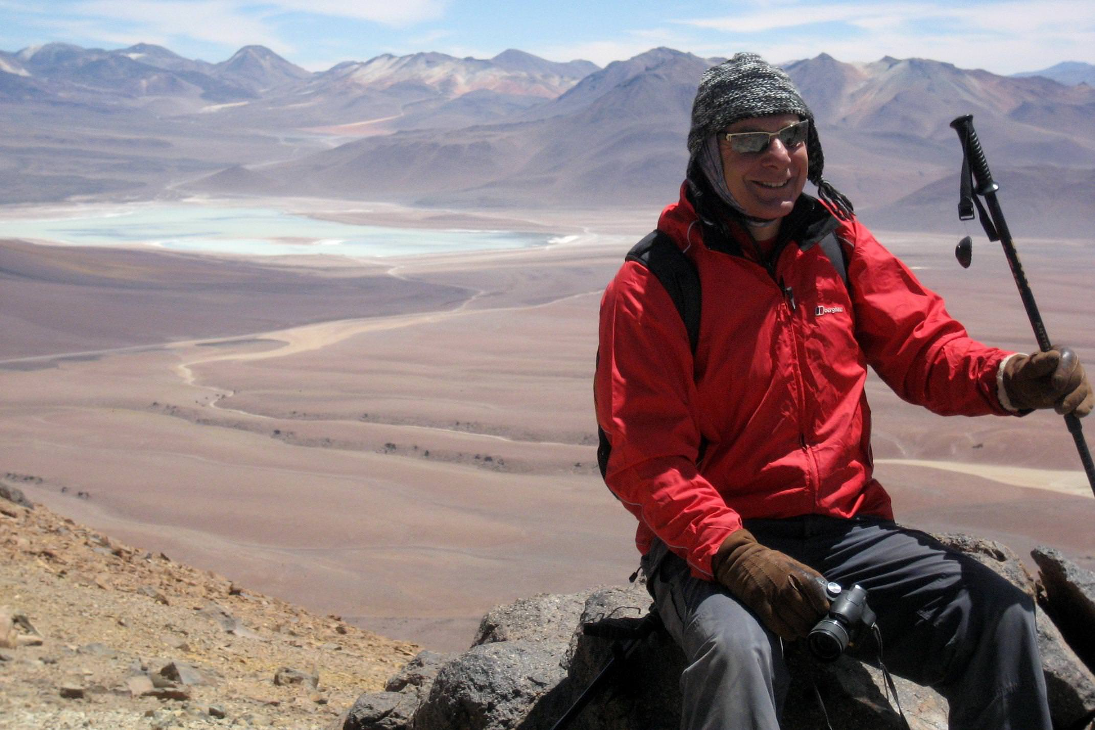 Chile atacama desert man in red sitting at summit of toco volcano
