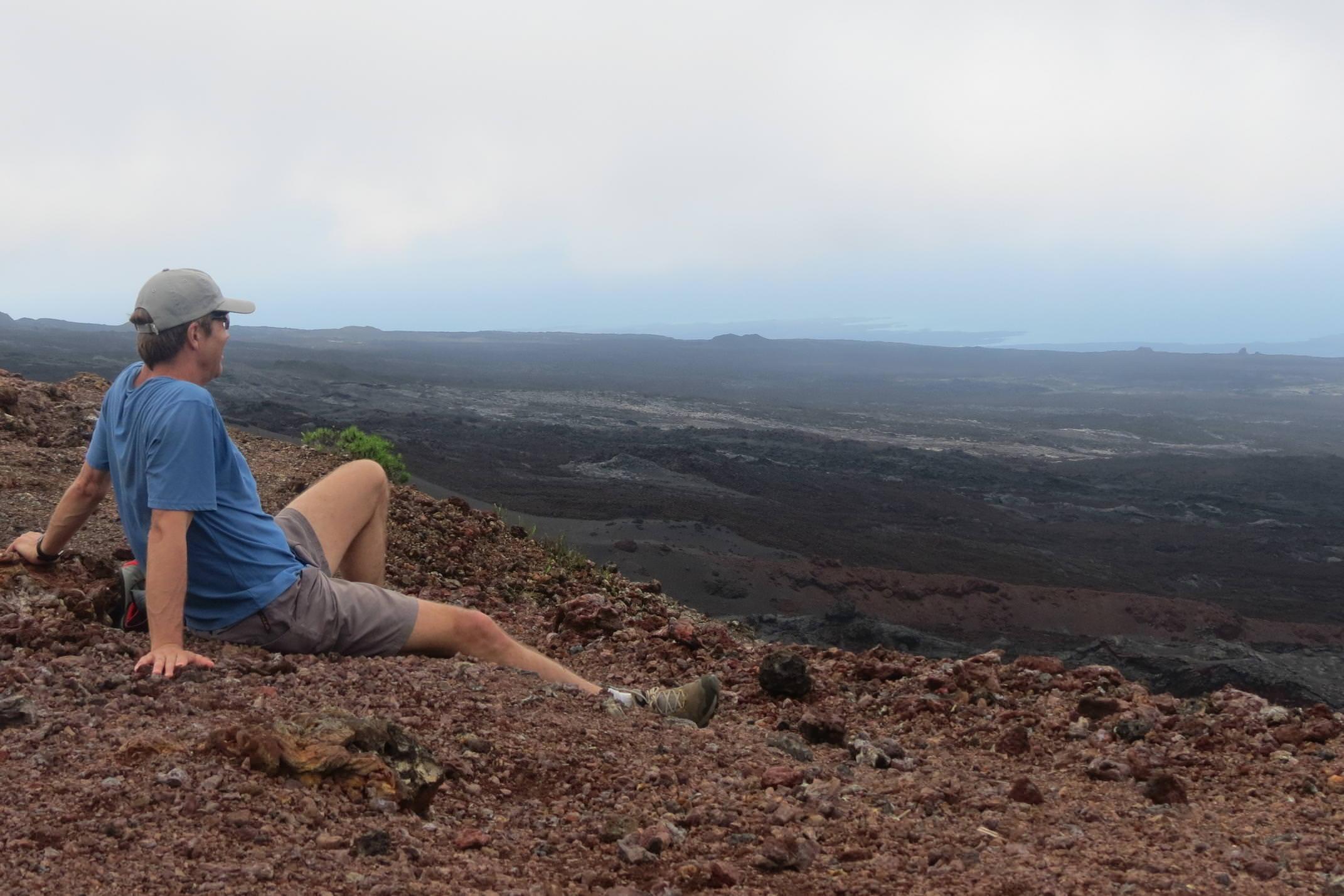 Ecuador galapagos islands isabela cerro negro volcano crater solo man looking out over lava field