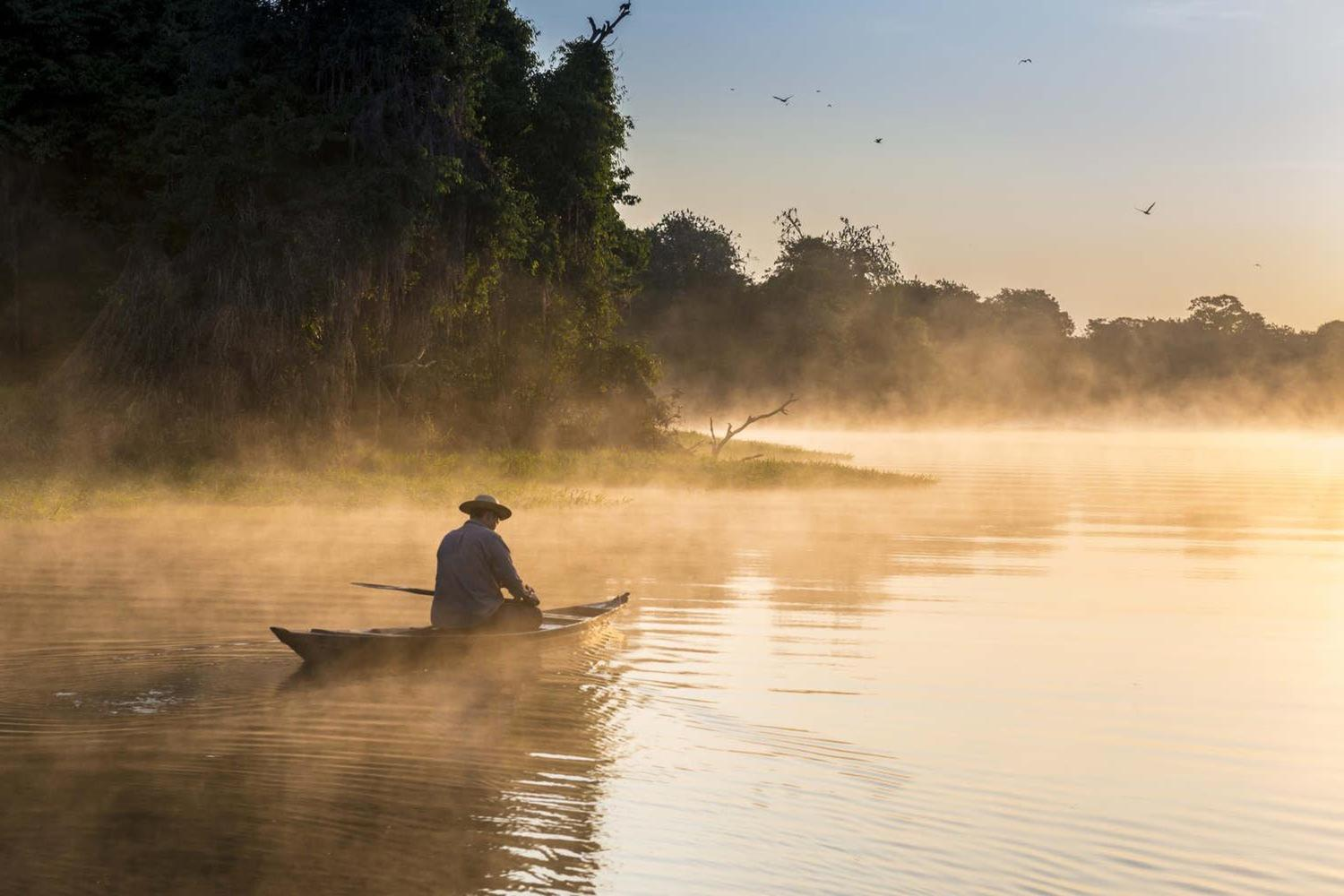 brazil-amazon-man-on_boat-sailing-the-river-in-the-early-morning
