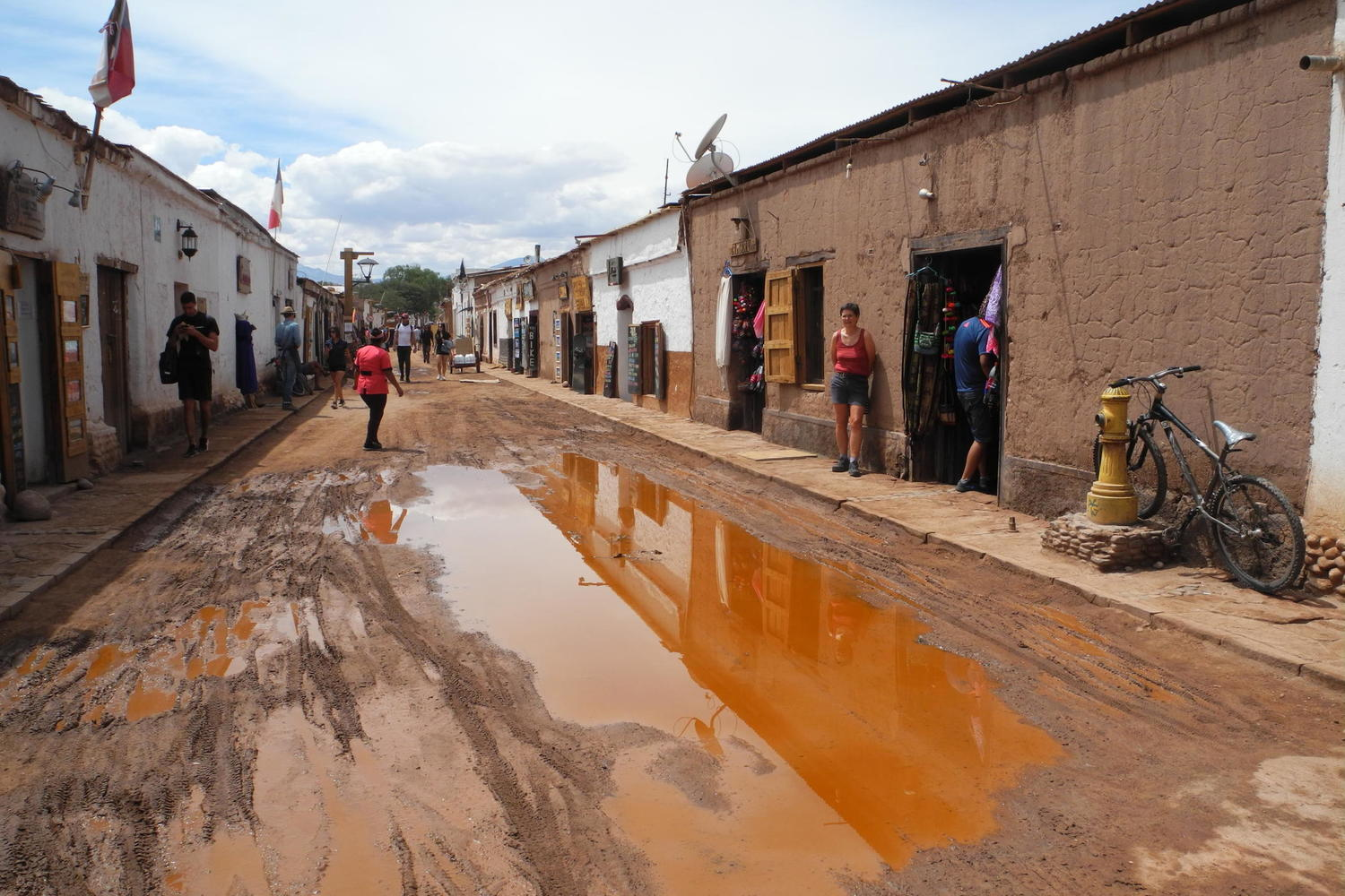 Rare puddles turn the streets of San Pedro de Atacama orange