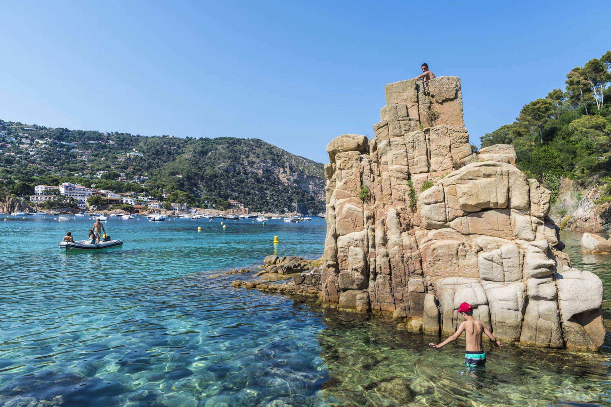 Spain catalonia aiguablava beach with sunbathers while a boat is heading to the beach in costa brava j2r